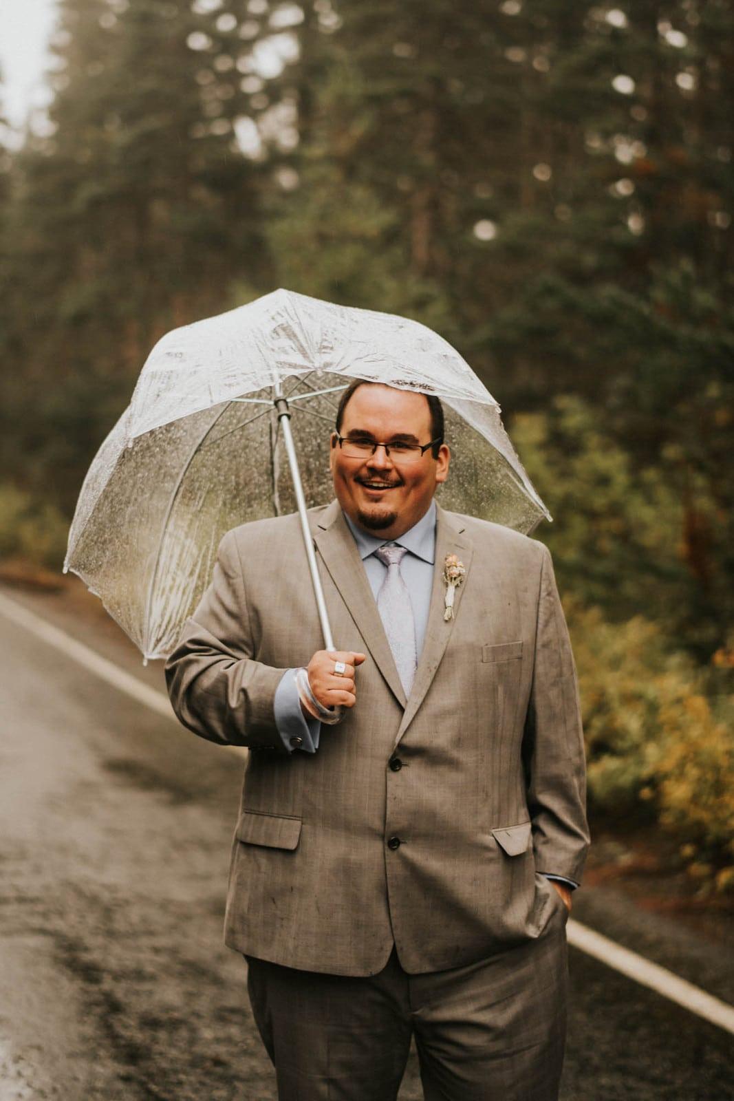 Groom standing with umbrella