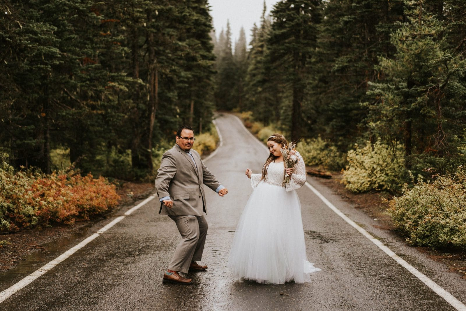 bride and groom dancing in the road