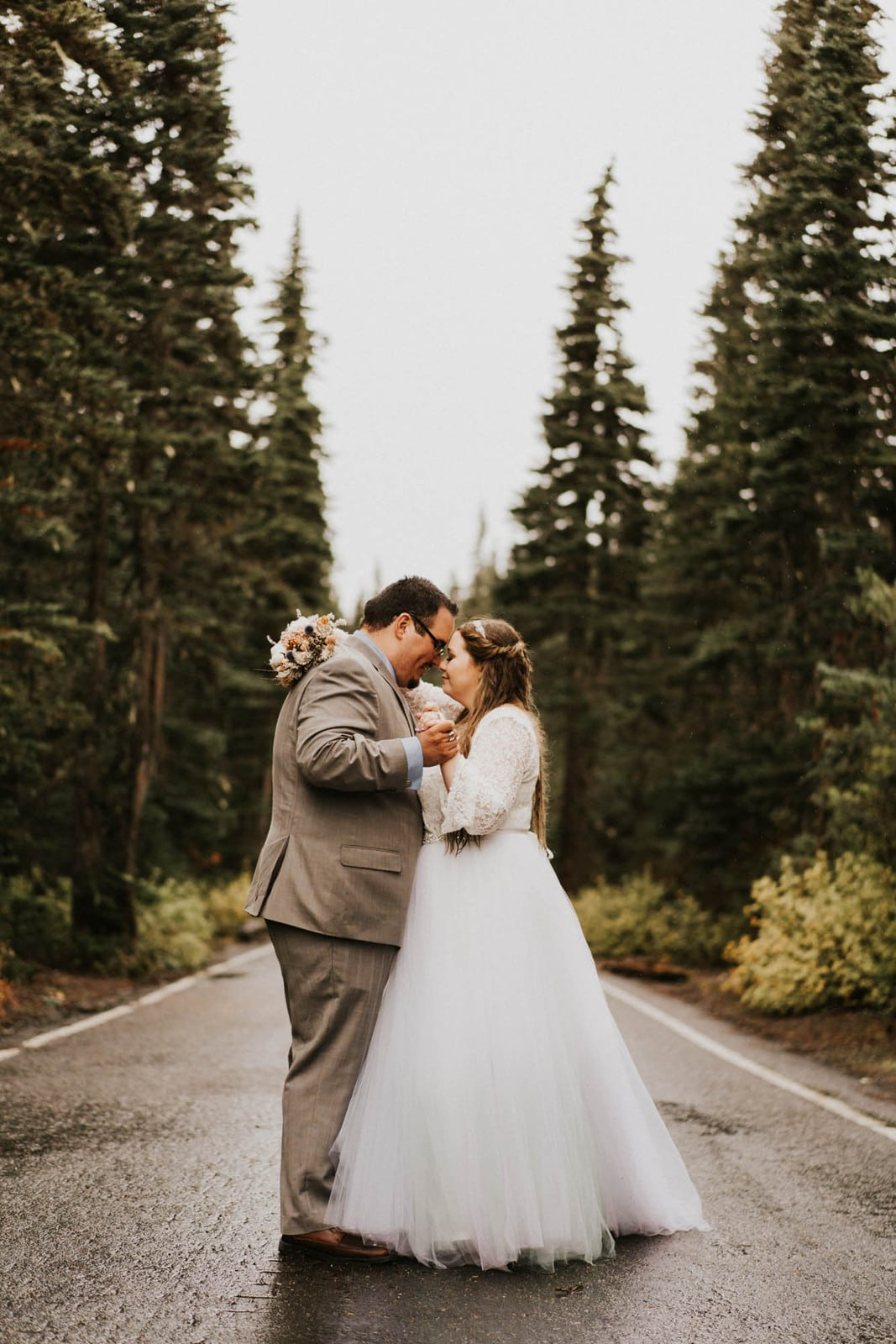 bride and groom slow dancing in the road