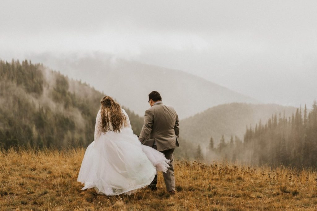 bride and groom walking toward mountain views