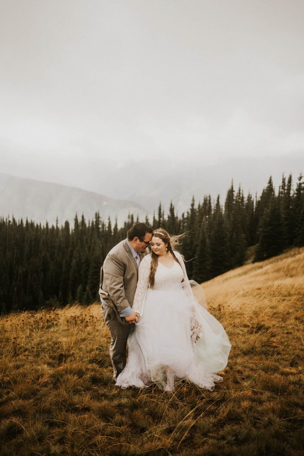 groom holding bride from behind at hurricane ridge elopement