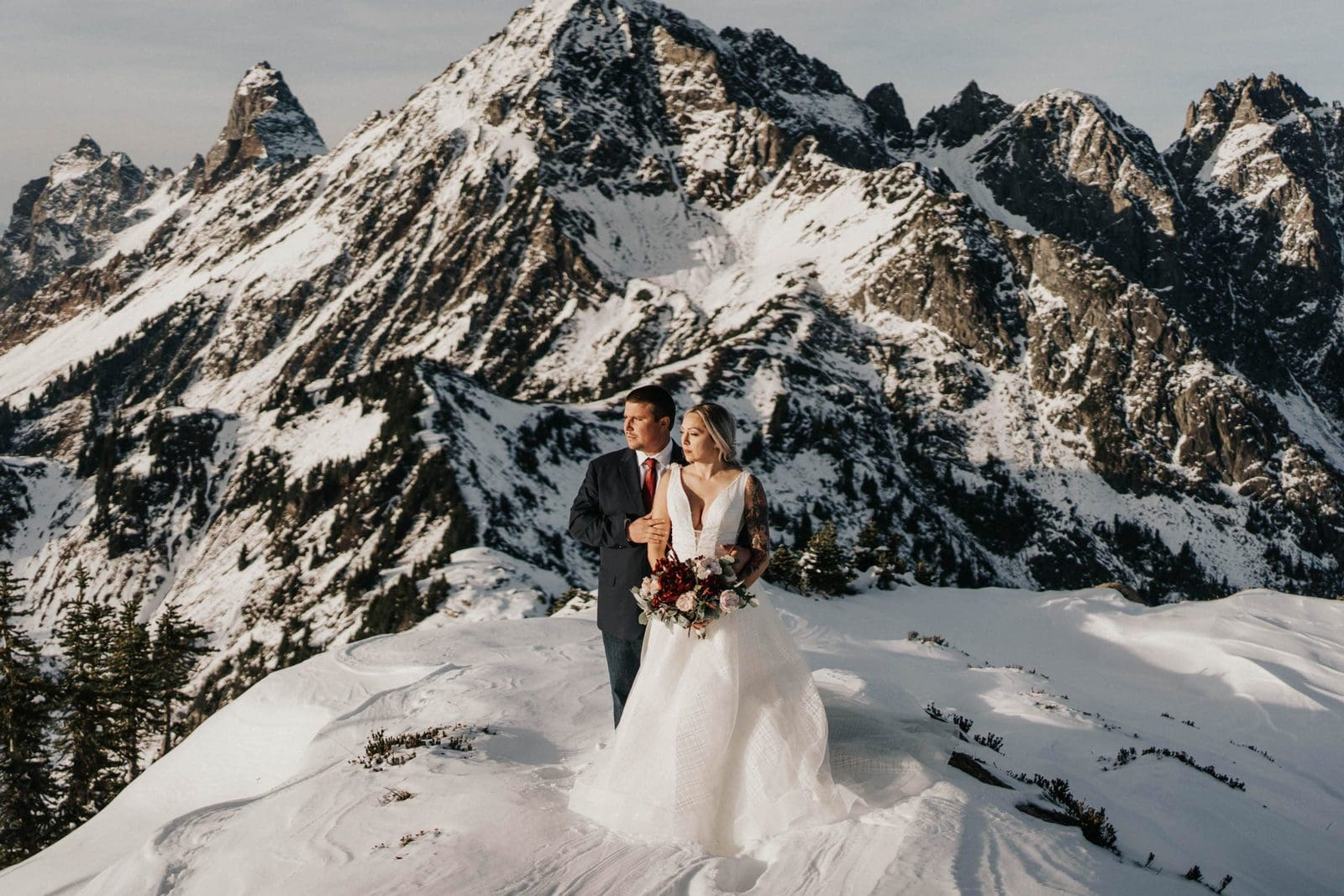 bride and groom standing in front of the mountains