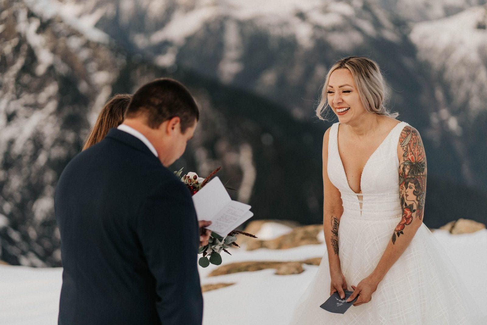 bride laughing at grooms vows at ceremony