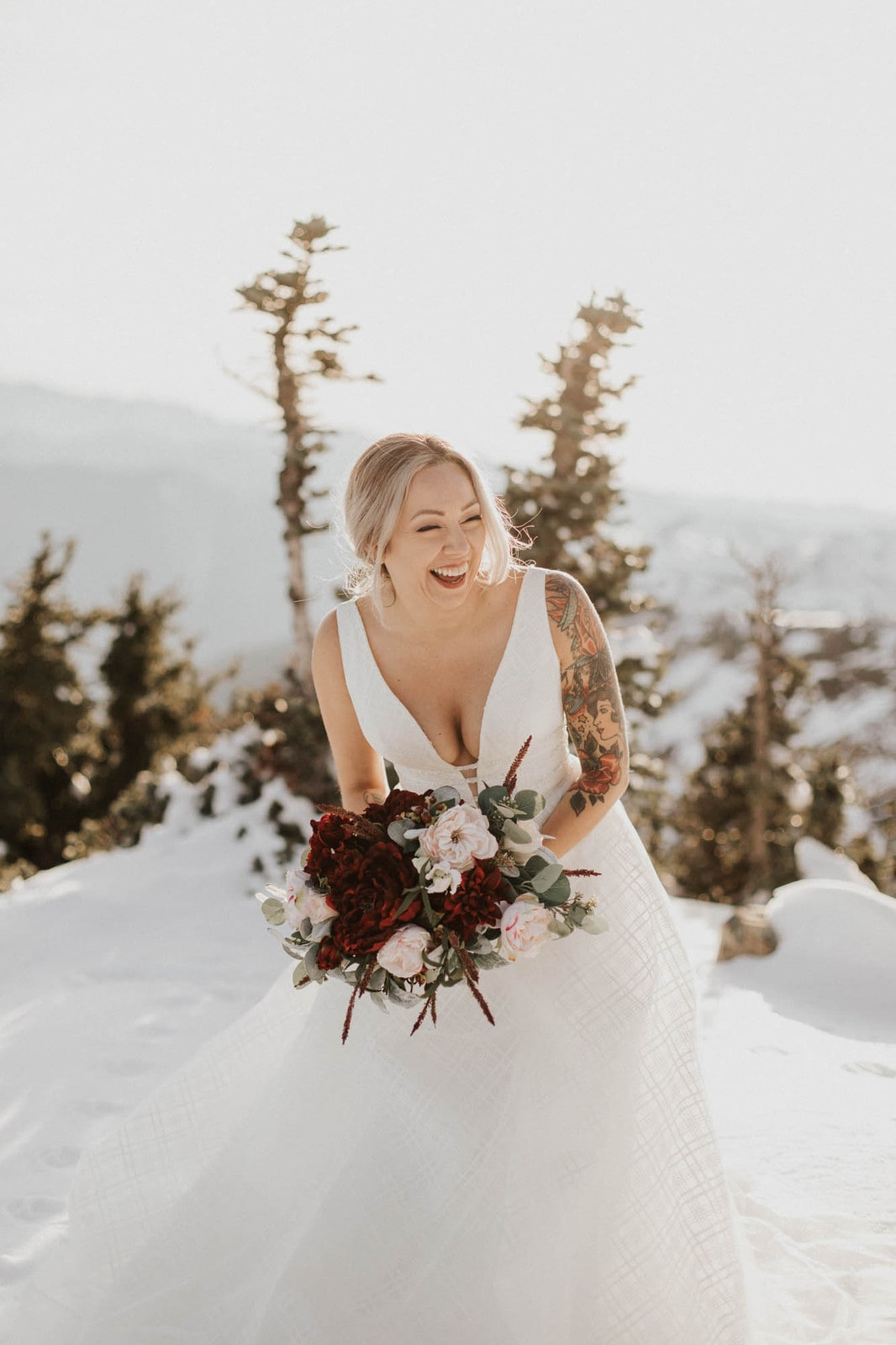 bride laughing and holding her bouquet