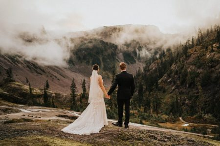 bride and groom looking out at mountain views at artist point elopement